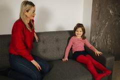Blond hair mom in red sweater sitting on sofa with her daughter. Beautiful woman stock photos