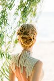 Blond blond hair is professionally made with braids in a magnificent hairstyle for a summer wedding image of a bride or royalty free stock photography