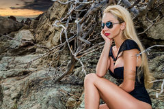 Blond hair sexy woman young girl model in sunglasses and elegant black and gold sexy swimsuit Royalty Free Stock Photo