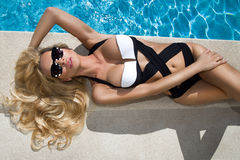 Blond hair sexy woman young girl model in sunglasses and elegant white and black sexy swimsuit Stock Images