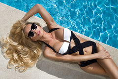 Blond hair sexy woman young girl model in sunglasses and elegant white and black sexy swimsuit lingerie Royalty Free Stock Photos