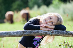 Blond hair small girl with clasped hands resting on fence Royalty Free Stock Photos