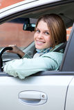 Blond hair woman driver looking back from car Royalty Free Stock Image