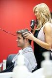 Blond hairdresser drying her customer's hair Stock Images