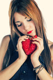 Blond haired female with heart in his hands. Blond haired woman with heart in his hands looking down royalty free stock images