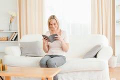 Blond-haired Frau, die ein Buch liest Stockfoto