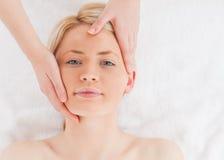 Blond-haired Frau, die eine Massage auf ihrem Gesicht erhält Lizenzfreie Stockbilder