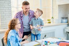 Adorable Family Celebrating Fathers Day. Blond-haired little boy standing on chair and looking at his laughing dad with wide smile while giving him handmade royalty free stock image