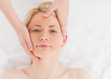 Blond-haired woman getting a massage on her face Royalty Free Stock Images
