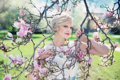 Blond Haired Woman Posing on Leafless Pink Flowered Tree Royalty Free Stock Images
