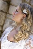Blond haired young bride. Side portrait of blond haired young bride in traditional white wedding dress; old wall in background stock photography