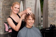 Blond hairstylist applying hair mousse spray. Royalty Free Stock Photo