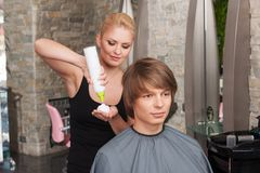 Blond hairstylist female with hair mousse spray. Stock Photos