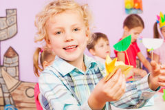 Blond handsome boy shows origami craft in class Stock Photo