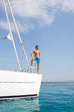 Blond handsome young man posing on sailing boat. Royalty Free Stock Photos