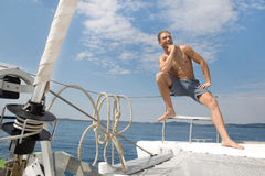 Blond handsome young man on sailing boat. Royalty Free Stock Photos