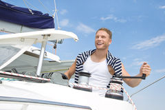 Blond handsome young man on sailing boat. Stock Photo