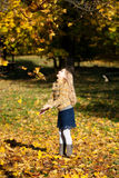 A blond happy girl throwing up the leaves. Happy girl, lucky and marry, throwing up the tree leaves in the autumn park Royalty Free Stock Image