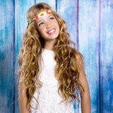 Blond happy hippie children girl smiling on blue wood Stock Photography