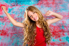 Blond happy kid girl in red happy with arms up Royalty Free Stock Image