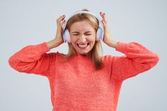 Blond in headphones listening bad music. Isolated on white Royalty Free Stock Photo