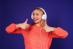 Blond in headphones showing double thumbs up. On violet Stock Images