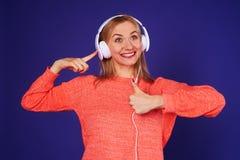 Blond in headphones showing thumbs up. Studio shot Stock Photo