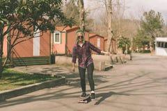 Blond hipsterflicka som rider en skateboard royaltyfri bild
