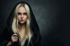 Blond in hood. Beautiful blond young woman in black hood looking at camera Royalty Free Stock Photo