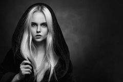Blond in hood. Beautiful blond young woman in black hood looking at camera, monochrome Royalty Free Stock Photos