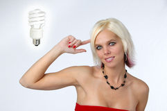 Blond with idea gesture. And electrical bulb on a neutral background royalty free stock images