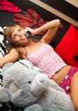 Blond im Bett mit Telefon Stockbilder