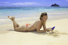 Blond im Bikini auf dem texting Strand Stockbilder