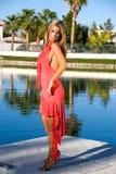 Blond im korallenroten Kleid. Lizenzfreies Stockfoto