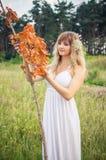Blond im weißen Kleid auf der Lichtung Lizenzfreie Stockbilder