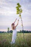 Blond im weißen Kleid auf der Lichtung Lizenzfreie Stockfotos