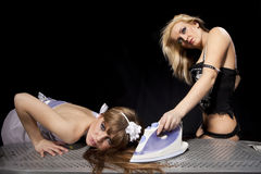Blond ironing redhaired woman Stock Photography
