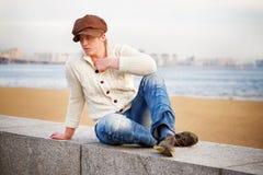 Blond kędzierzawy mężczyzna jest ubranym dziewiarską kurtkę i cajgi siedzi na Zdjęcia Royalty Free