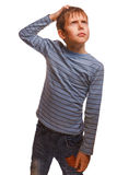 Blond kid boy in a striped sweater thinks Stock Image