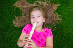 Blond kid children girl playing flute lying on grass. Backyard lawn Stock Image