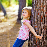 Blond kid girl on autumn tree trunk Stock Images