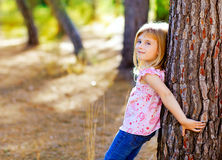 Blond kid girl on autumn tree trunk Stock Photography