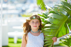 Blond kid girl at banana tree leaves in bright day Royalty Free Stock Photography