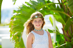Blond kid girl at banana tree leaves in bright day Royalty Free Stock Photos