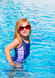 Blond kid girl in blue pool posing with sunglasses. Smiling stock images