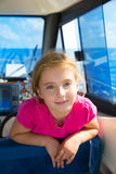 Blond kid girl at boat indoor sailing smiling happy Stock Images