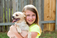 Blond kid girl with chihuahua pet dog playing Royalty Free Stock Photos