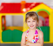 Blond kid girl crossed arms in toy house Stock Photos