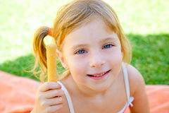 Blond kid girl eating one salted bagel Royalty Free Stock Photo