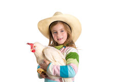 Blond kid girl farmer holding white hen on arms Royalty Free Stock Images